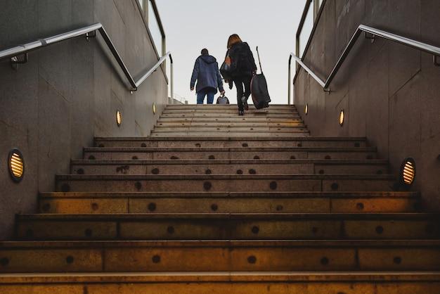 Silueta, de, dois passageiros, com, seu, malas, bonde, escalando, um, escada