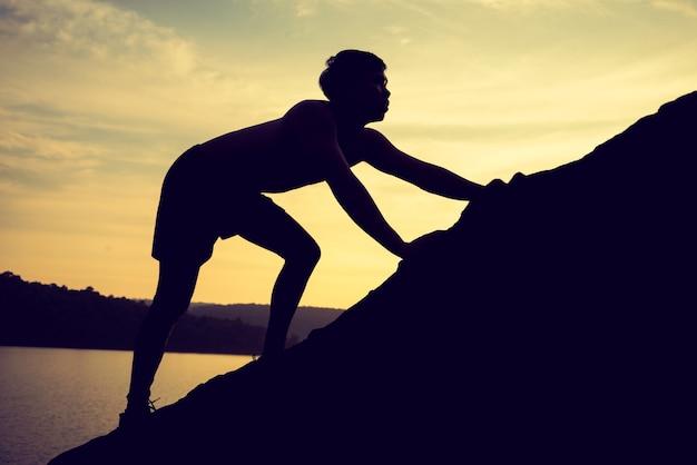 Silueta, de, escalada homem, em, pôr do sol