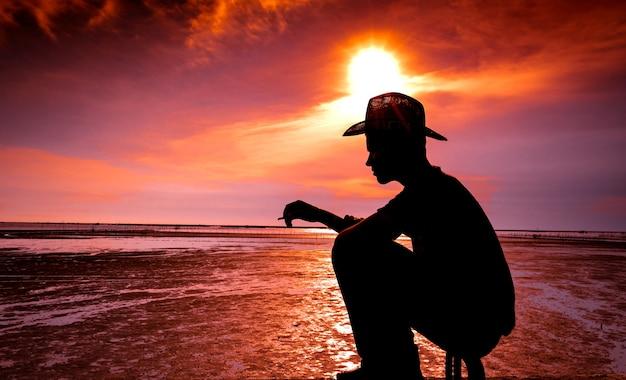 Silueta, de, homem jovem, sentando praia, por, a, mar, e, fumar