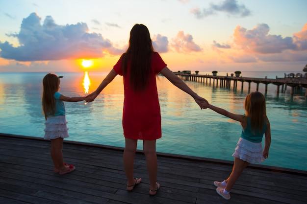 Silueta, de, jovem, mãe, e, dois, dela, garotinhas, em, pôr do sol