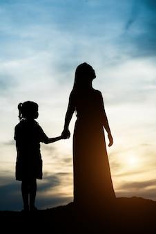 Silueta, de, mãe, com, dela, filha, ficar, e, pôr do sol