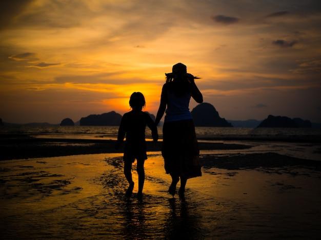 Silueta, de, mãe, segurando, amável, mão, e, passeio, praia, durante, pôr do sol