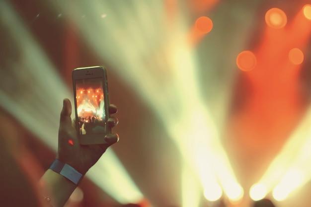 Silueta, de, mãos, com, um, smartphone, em, um, concerto