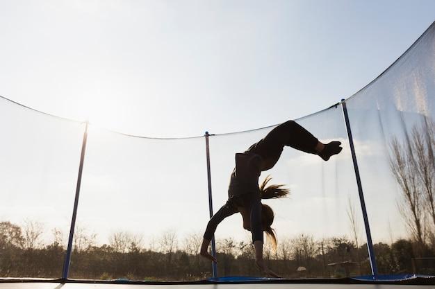 Silueta, de, menina, pular, cabeça baixo, ligado, trampoline, contra, a, céu azul