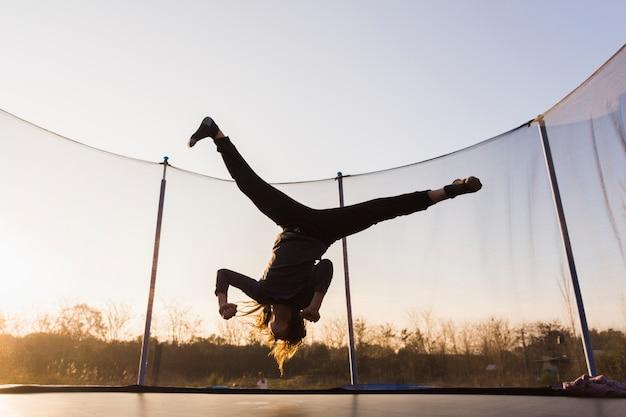 Silueta, de, menina, pular, ligado, um, trampoline, fazendo, divisão