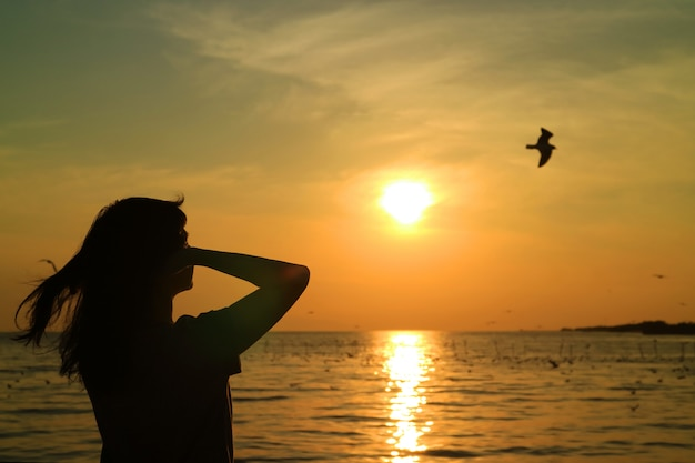 Silueta, de, mulher jovem, observar, a, sol eleva-se, ligado, céu dourado, com, um, voando, pássaro
