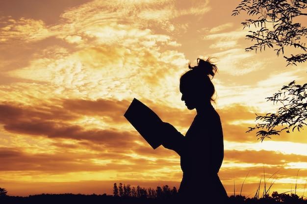 Silueta, de, mulher, livro leitura, em, céu ocaso