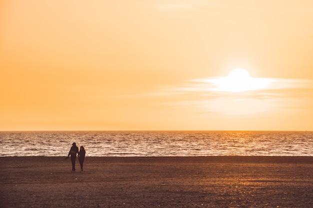 Silueta, de, par caminhando, praia, em, pôr do sol, almeria, espanha