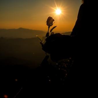 Silueta, de, par, segurando, rosa, ligado, colina, em, a, pôr do sol, tempo, skyline, ligado, fundo