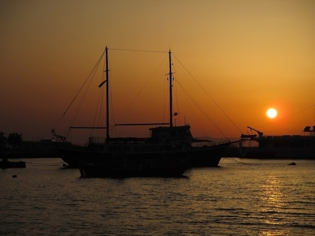 Silueta, de, sailboat, contra, a, deslumbrante, pôr do sol, sobre, a, porto velho, de, mykonos, grécia