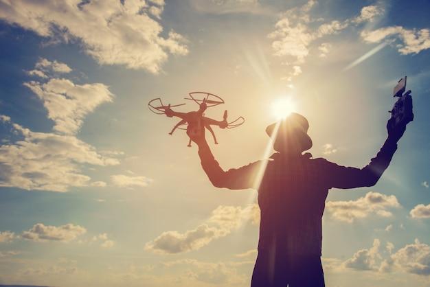 Silueta, de, um, homem jovem, tocando, com, a, zangão, em, pôr do sol