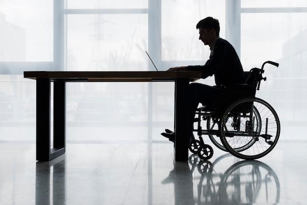 Silueta, de, um, homem negócios, sentando, ligado, cadeira rodas, usando, laptop, ligado, tabela, frente, janela