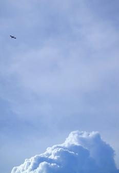 Silueta, de, um, voando, avião, ligado, luminoso azul, céu nublado, com, nuvens cumulus