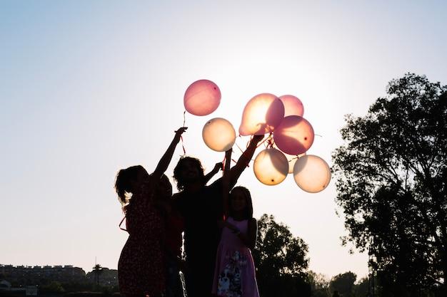 Silueta, família, segurando, balões