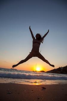 Silueta, jovem, mulher, pular, pernas, braços, abertos, praia