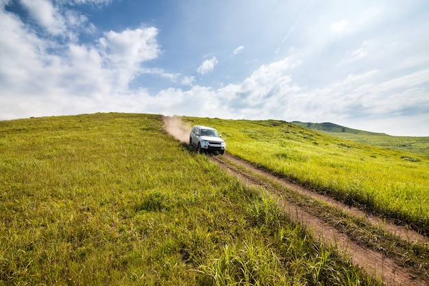 Silver suv desce a colina por uma estrada de terra