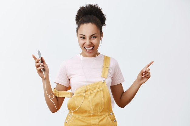 Sim, apenas ouça essa nova faixa. retrato de mulher jovem e feliz animada com pele escura, usando um macacão amarelo e alça no braço, dançando e sacudindo os braços, segurando um smartphone, curtindo música nos fones de ouvido