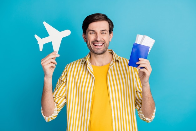 Sim, as fronteiras estão abertas. homem alegre positivo segurar papel cartão bilhetes de avião desfrutar de uma viagem ao exterior quarentena cobiçada usar roupa branca isolada sobre fundo de cor azul