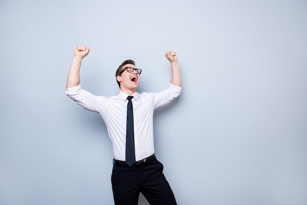 Sim! bem sucedido jovem estudante bonito está comemorando. ele está em uma roupa formal e óculos pretos elegantes, em puro espaço, com as mãos levantadas