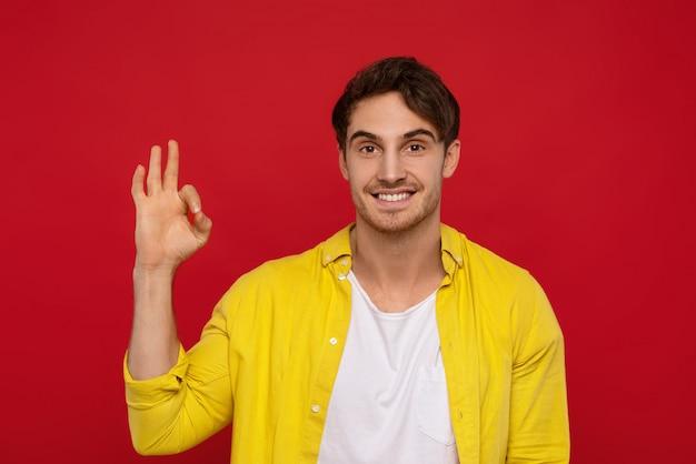 Sim, está bem. homem bonito positivo na camisa amarela, mostrando sinal de ok com uma mão, tem um grande sorriso, sendo de alto espírito