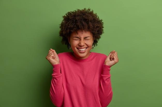 Sim, esta é minha oportunidade. mulher afro-americana alegre regozija-se com o sucesso, fecha os punhos em triunfo, deseja vencer, celebra a conquista, veste um suéter rosado, isolada na parede verde