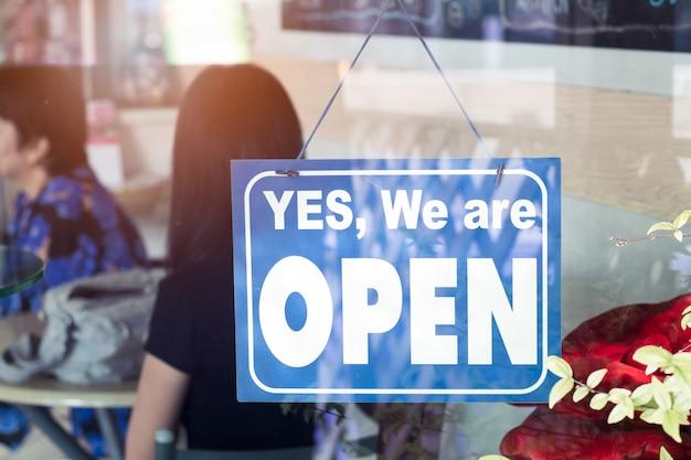 Sim, estamos sinal aberto pendurado na porta do café.