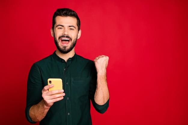 Sim, eu melhor! homem em êxtase usando smartphone usuário de mídia social ganha loteria de fãs online obter muitos seguidores de blog gritar levantar os punhos usar camisa verde