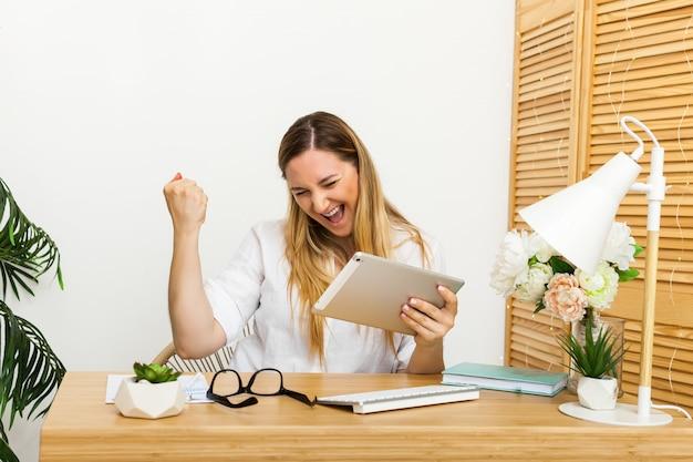 Sim. feliz mulher excitada em casa, estação de trabalho, triunfando com as mãos levantadas