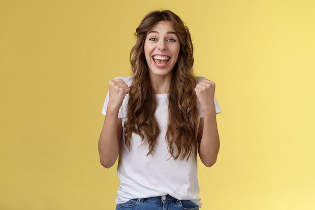 Sim, finalmente sucesso. alegre entusiasta feliz menina bomba punhos levantar mãos vitória alegria celebração gesto sorrindo amplamente aliviado ganhando loteria divertido stand fundo amarelo triunfando.