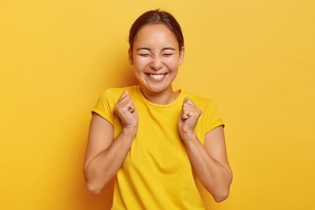 Sim, finalmente sucesso! alegre garota coreana cerrou os punhos em triunfo, fecha os olhos de felicidade e alegria, tem sorriso cheio de dentes, veste roupa casual, isolada na parede amarela, triunfa vitória