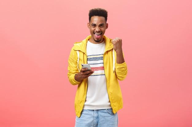 Sim, ganhei. retrato de homem afro-americano feliz, animado e satisfeito com a barba levantando o punho em vitória e triunfo gesto de júbilo segurando o smartphone vencendo no jogo do telefone online sobre a parede rosa