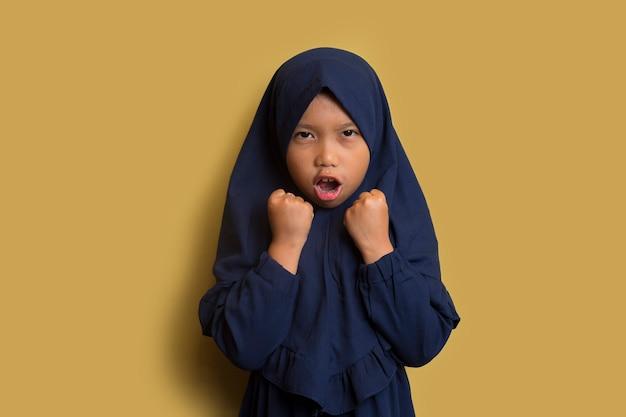Sim. garotinha asiática muçulmana hijab feliz sacudindo os punhos fazendo gesto de vencedor
