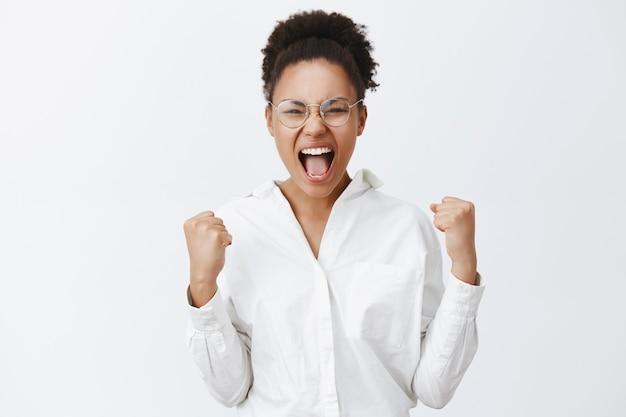 Sim meninas, nós conseguimos. retrato de uma mulher africana bonita triunfante de camisa branca e óculos, levantando os punhos cerrados e gritando de espanto e felicidade, celebrando a vitória sobre a parede cinza