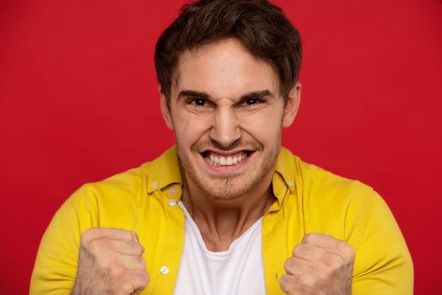Sim, nós conseguimos! homem excitado na camisa amarela, mostrando o gesto sim, mantém os punhos cerrados no gesto da vitória, sente-se otimista,