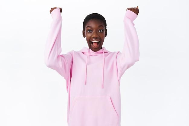 Sim, parabéns. divertida e feliz linda garota afro-americana vencendo, erguendo os punhos e sorrindo, ouça notícias incríveis e incríveis