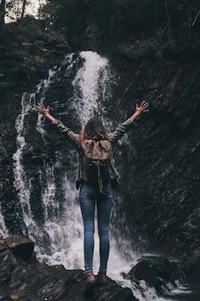 Sim! retrovisor de corpo inteiro de mulher jovem com mochila, mantendo as mãos levantadas em pé perto da cachoeira