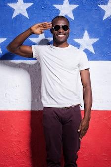 Sim senhor! africano jovem feliz em óculos de sol, segurando a mão perto da testa e sorrindo em pé contra a bandeira americana