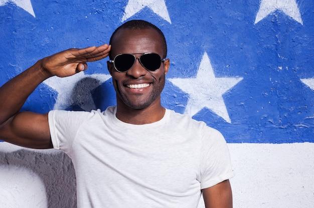 Sim senhor sim! africano jovem feliz em óculos de sol, segurando a mão perto da testa e sorrindo em pé contra a bandeira americana