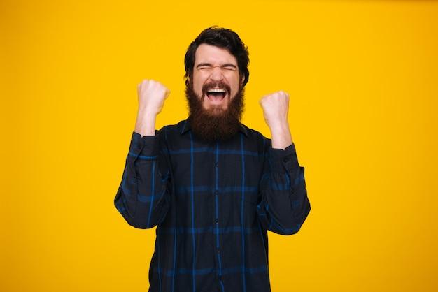 Sim!!! um vencedor barbudo, comemorando com os braços para cima e olhos fechados sobre parede amarela