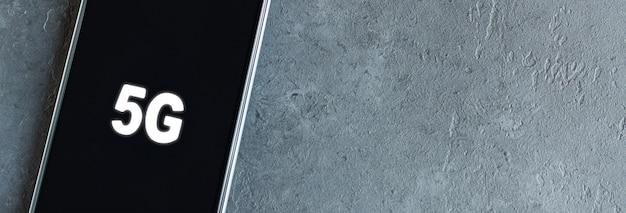 Símbolo 5g em uma tela preta do smartphone. rede global de alta velocidade.