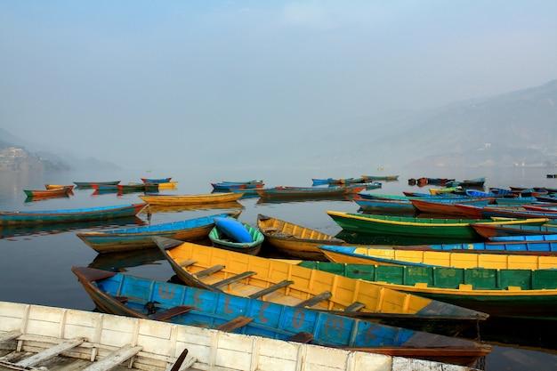 Símbolo colorido dos barcos da costa do lago phewa com névoa na manhã, pokhara nepal.