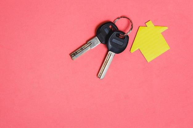 Símbolo da casa com duas chaves de prata sobre fundo rosa