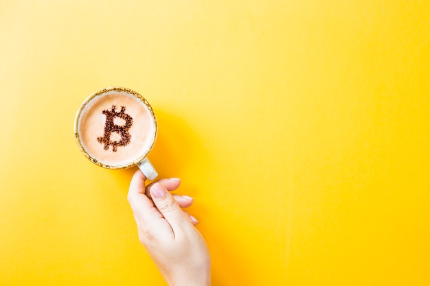 Símbolo da moeda criptográfica bitcoin em uma xícara de café sobre um fundo amarelo