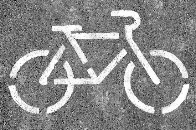 Símbolo de bicicleta preto e branco em fundo de asfalto texturizado
