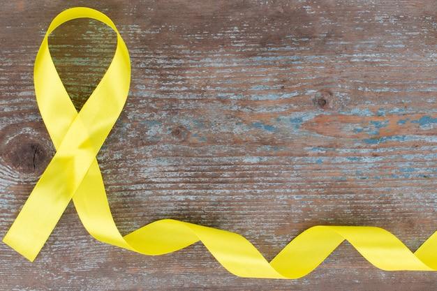 Símbolo de conscientização do câncer infantil de fita amarela na madeira