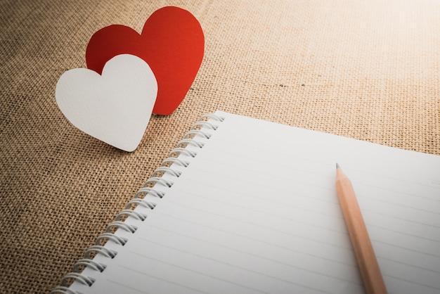 Símbolo de corações vermelhos e notebook na superfície do saco de tecido