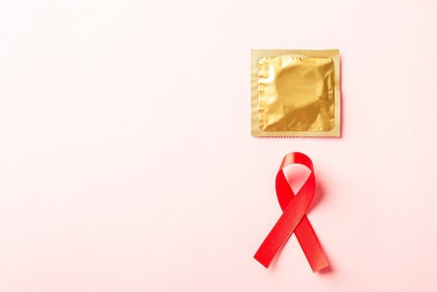 Símbolo de fita com laço vermelho hiv aids e preservativo