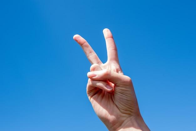 Símbolo de gesto número dois, dois dedos de uma mão de mulher caucasiana, mostrando um gesto de vitória ou paz no céu azul