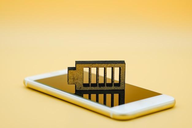 Símbolo de ícone de bateria de madeira no telefone inteligente.