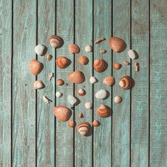 Símbolo de lareira feito de conchas do mar, pedras e corais na parede de madeira. conceito de amor. postura plana.